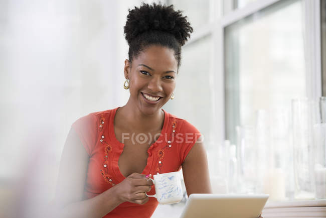 Mid adult woman in holding digital tablet and having cup of coffee in kitchen. — Stock Photo