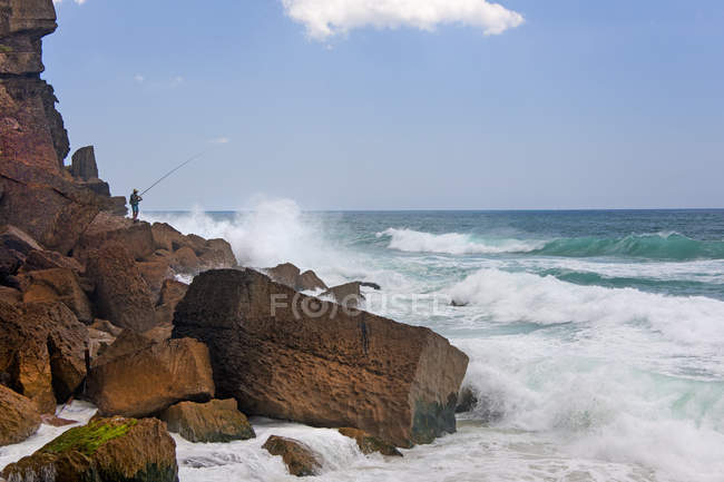 Waves breaking on shore with fishing person on Atlantic coastline of Portugal. — Stock Photo