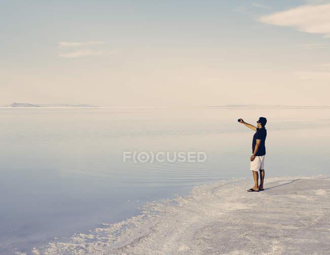 Man steht am Rand des überfluteten Salzsee von Bonneville in der Abenddämmerung und Aufnahme mit Smartphone in der Nähe von Wendover, Utah, Usa. — Stockfoto
