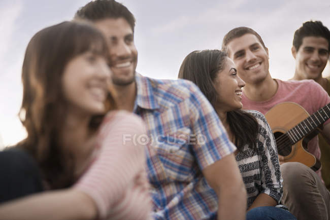 Group of people hanging out at roof party with friends and guitar. — Stock Photo
