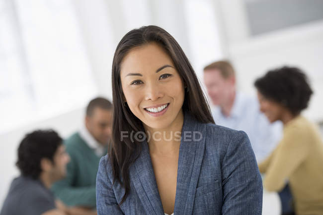 Cheerful businesswoman standing in meeting room with colleagues in background. — Stock Photo