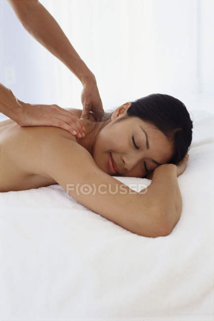 Young woman lying on front and having shoulder massage. — Stock Photo