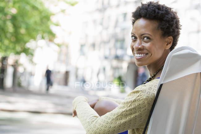 Mujer sentada en silla de camping, sonriendo y mirando por encima del hombro en la ciudad . - foto de stock