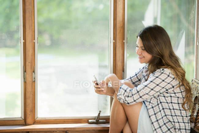 Junge Frau sitzt am Fenster und hält Smartphone. — Stockfoto
