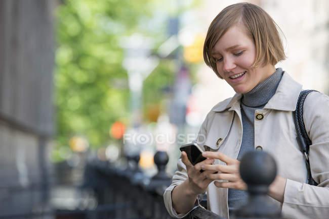 Mulher adulta média em jaqueta usando smartphone na cidade . — Fotografia de Stock