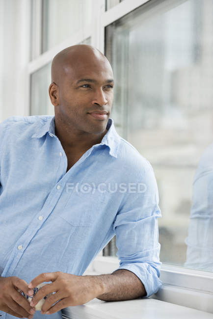 Mid adult man with cup of coffee looking through window. — Stock Photo