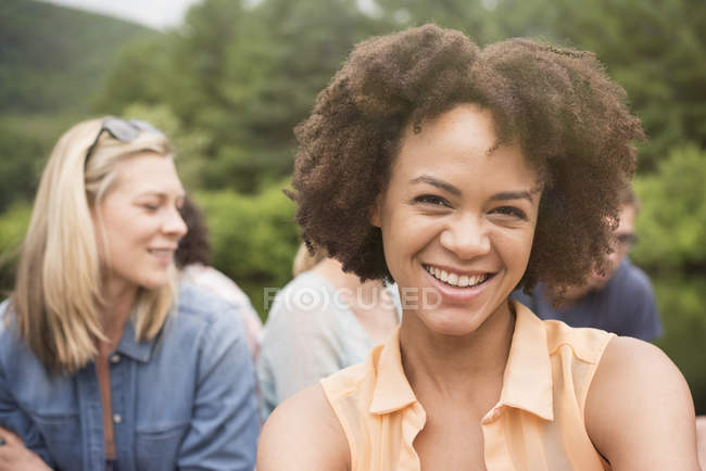 Young woman with afro smiling in group of friends outdoors. — Stock Photo