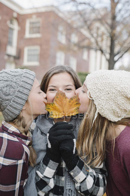 Teenage girls kissing on cheek s friend with autumn leaf in front of face. — Stock Photo