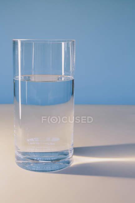 Bicchiere di acqua filtrata su superficie bianca . — Foto stock
