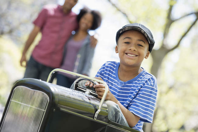 Boy riding old fashioned toy peddle car while parents watching in sunny park. — Stock Photo