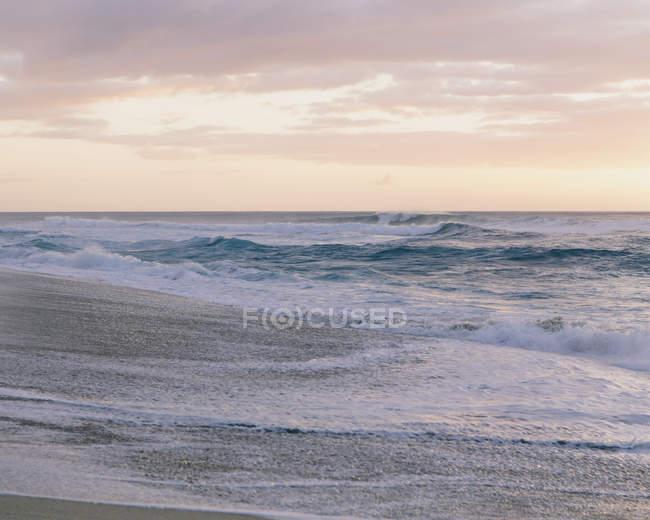 Волны и серфинга на песчаный пляж на закате. — стоковое фото