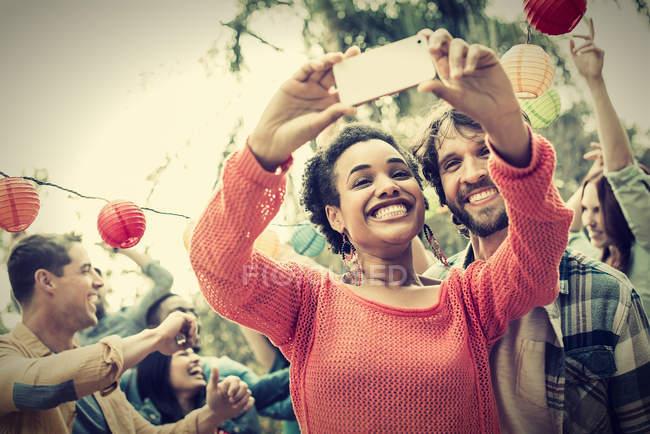 Mujer alegre y hombre tomando selfie en fiesta de baile al aire libre . - foto de stock