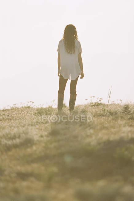 Жінка в білі сорочки з довгим волоссям стоячи на відкритому повітрі, задній вид. — стокове фото