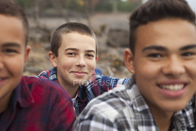 Teenage boys resting on shore of lake. — Stock Photo