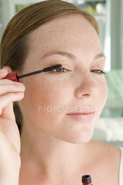 Junge Frau trägt Wimpern mit Wimperntusche auf, Porträt. — Stockfoto