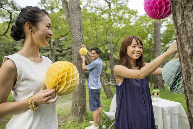 Group of people hanging paper lanterns on trees in woodland. — Stock Photo
