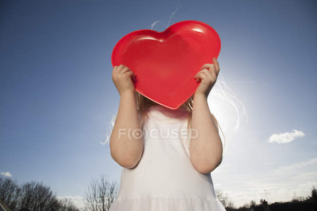 Low angle view of girl in white dress holding red heart shape in front of obscured face. — Stock Photo