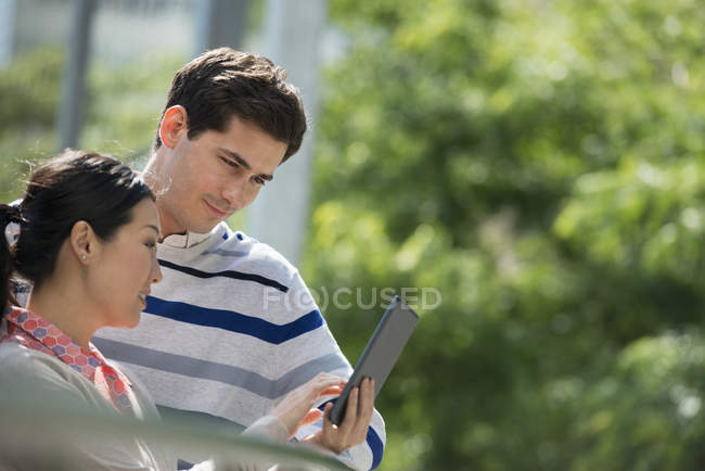 Man and woman sharing digital tablet in city park. — Stock Photo
