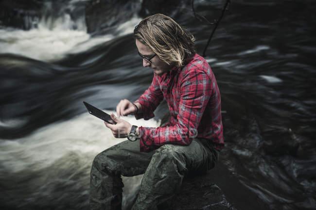 Uomo che si siede dal ruscello che scorre veloce e utilizza la compressa di digital. — Foto stock