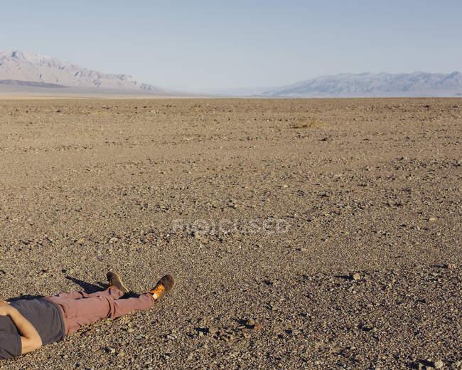 Vue en coupe de l'homme étendu sur le sol dans le désert du parc national de Death Valley, Californie, États-Unis . — Photo de stock
