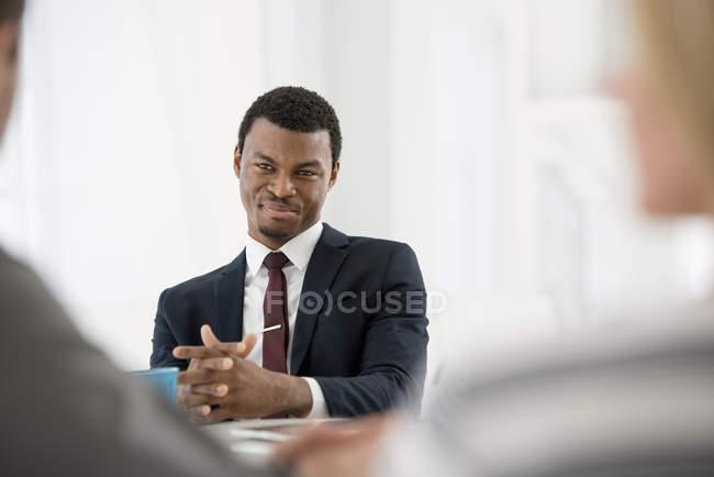 Junger Geschäftsmann im Anzug mit Händen umklammert mit Treffen mit paar — Stockfoto