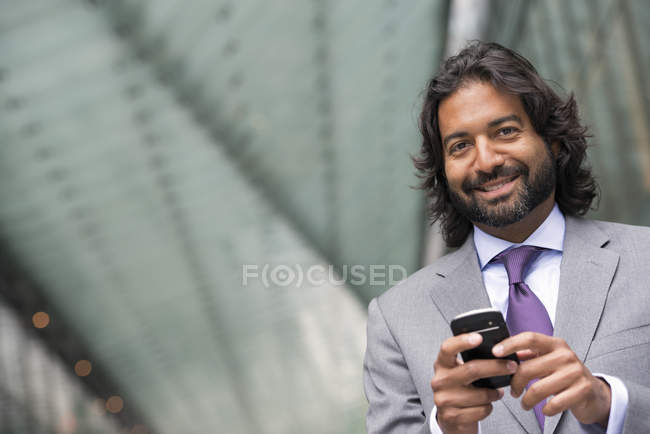 Man in business suit with beard and curly hair using smartphone. — Stock Photo