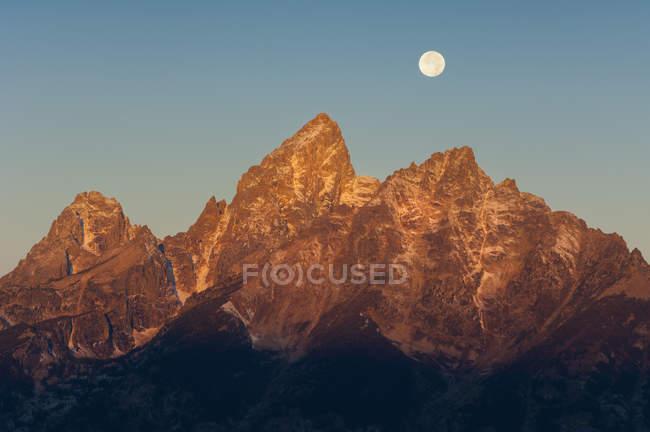 Cordillera dentada en el Parque Nacional Grand Teton con luna llena en el cielo . - foto de stock
