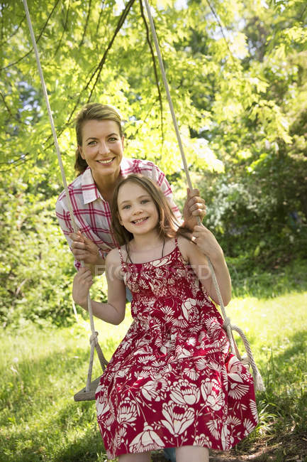 Reife Frau und Mädchen in Sundress auf Schaukel im Garten. — Stockfoto