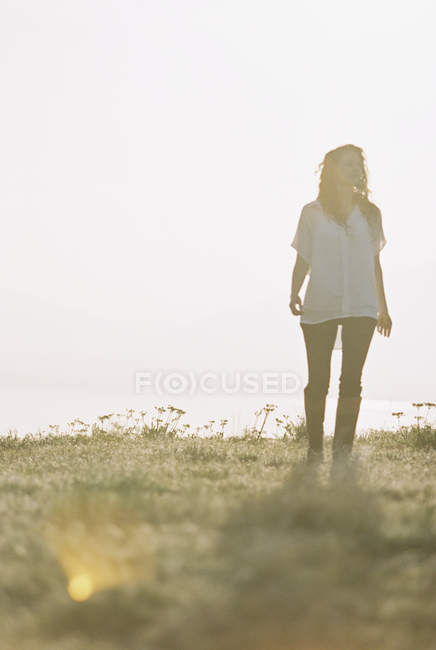 Woman in white shirt with long hair standing outdoors and looking away. — Stock Photo