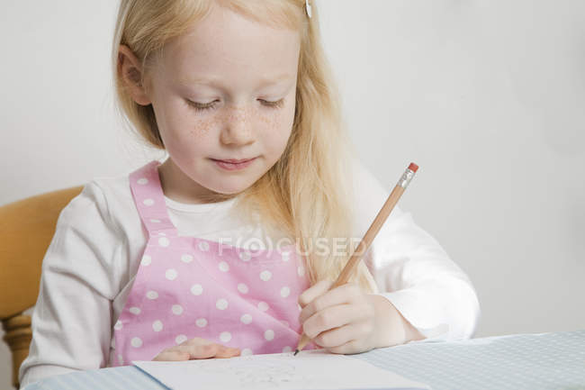 Elementary age blonde girl sitting at table and drawing with pencil. — Stock Photo