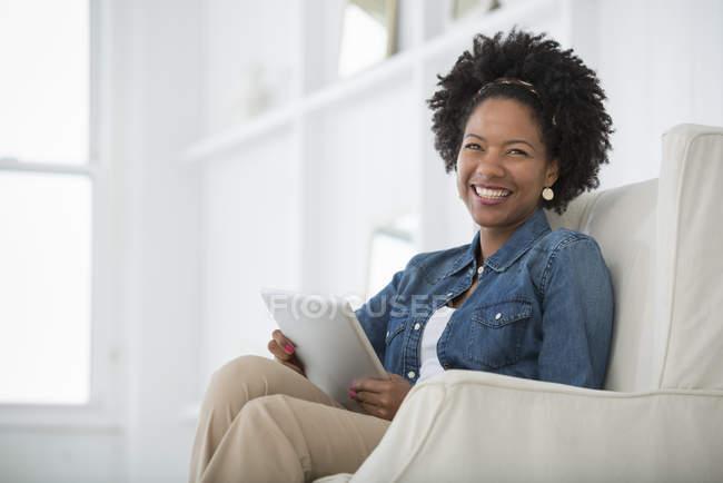 Mitte erwachsene Frau sitzt im Sessel mit digitalem Tablet und lächelt. — Stockfoto