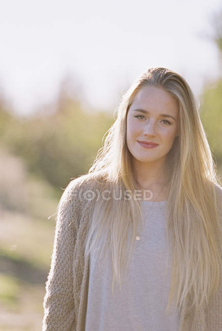Portrait of young adult woman with long blonde hair in garden. — Stock Photo