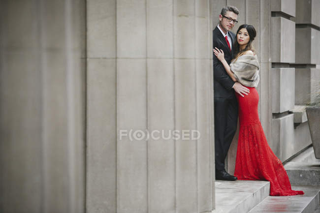 Woman in long red evening dress with fishtail skirt and fur coat embracing man in suit on steps of building. — Stock Photo