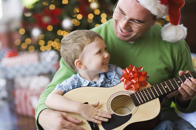 Отец и сын сидят у елки и играют на гитаре . — стоковое фото
