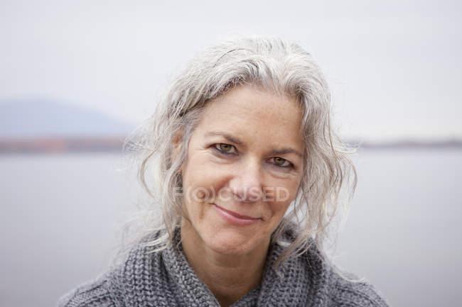 Зрелая женщина смотрит в камеру на берегу озера . — стоковое фото