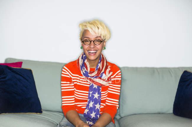 Mujer de raza mixta con cabello rubio en Ronda sentados en sofá y riendo - foto de stock