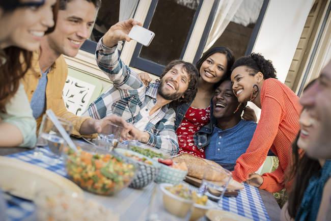 Groupe d'hommes et de femmes autour de table et prise selfie. — Photo de stock