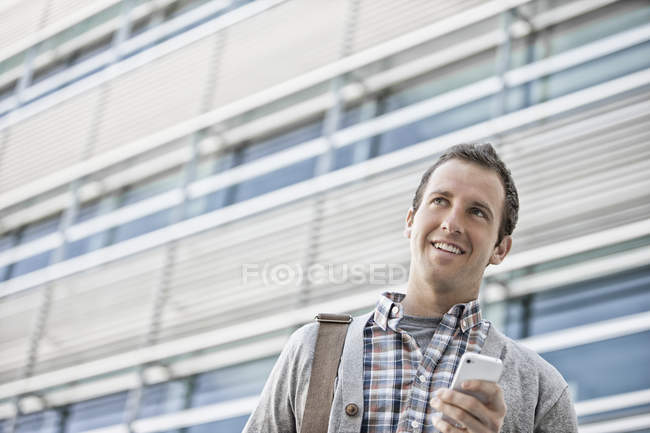 Man in checked shirt with open collar holding smartphone. — Stock Photo