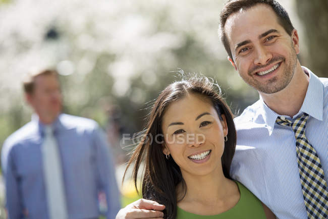 Couple standing side by side and smiling in camera with man in background. — Stock Photo