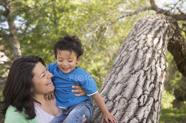 Мама играет с сыном в парке у высокого ствола дерева . — стоковое фото