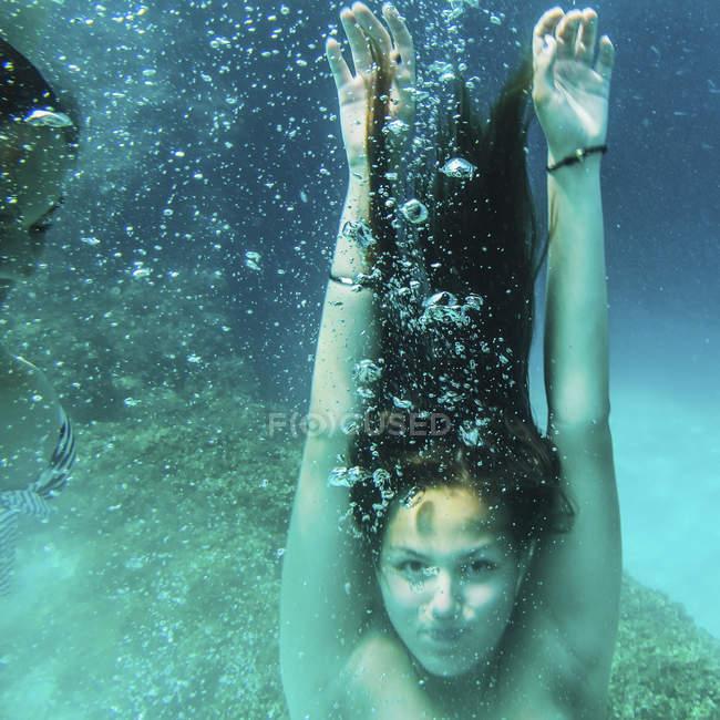 Young women diving underwater in ocean with bubbles. — Stockfoto
