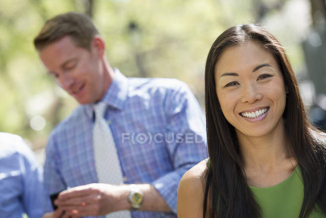 Mid adult woman smiling and looking in camera with businessmen talking in background. — Stock Photo