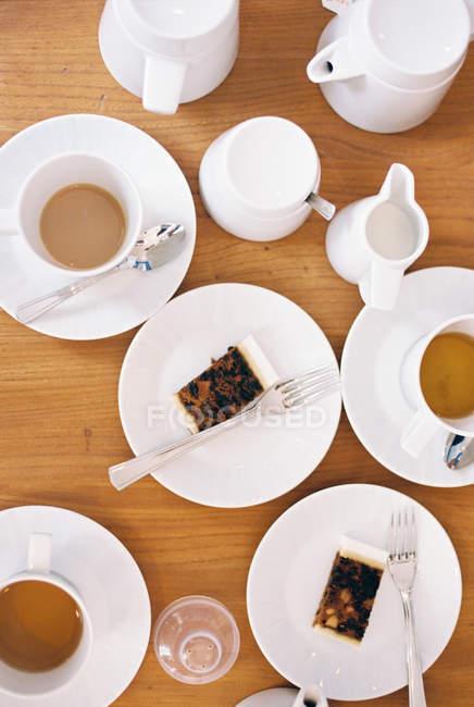 Vista superiore della tavola apparecchiata con tazze di tè, brocche di latte e fette di torta di frutta su piastre — Foto stock