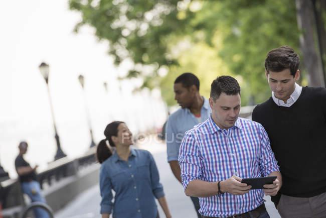 Quattro persone che camminano per strada e l'uomo medio adulto utilizzando tablet digitale . — Foto stock