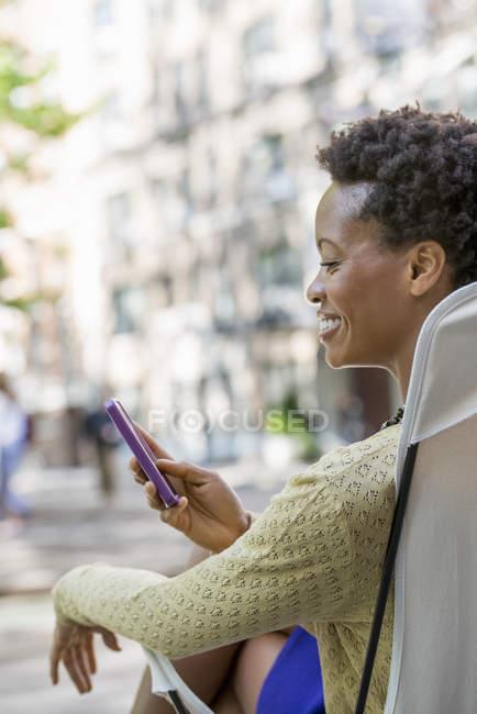 Mujer sentada en silla de camping en el parque de la ciudad y comprobando el teléfono . - foto de stock