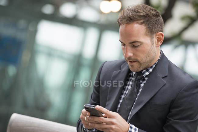 Hombre de traje de negocios con pelo corto usando smartphone en la calle . - foto de stock