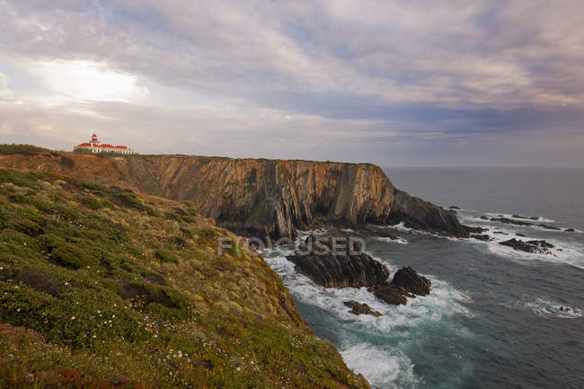Lighthouse on headland on Atlantic coastline cliff. — Stock Photo