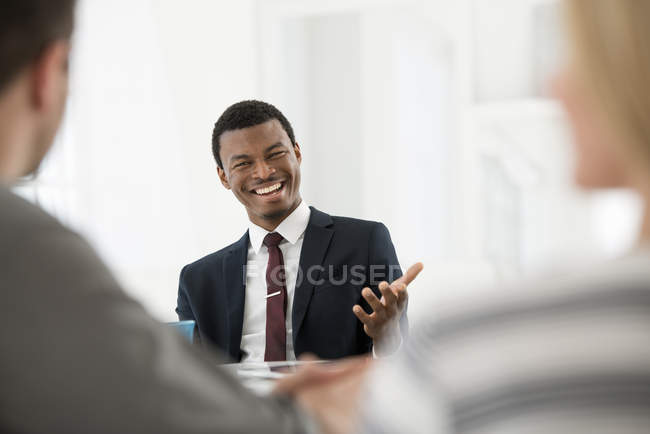 Junger Geschäftsmann im Anzug mit Tasse Kaffee mit Treffen mit paar — Stockfoto