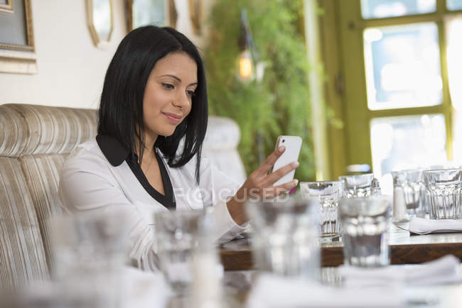 Mid adult woman using smartphone at cafe table with drinking glasses. — Stock Photo