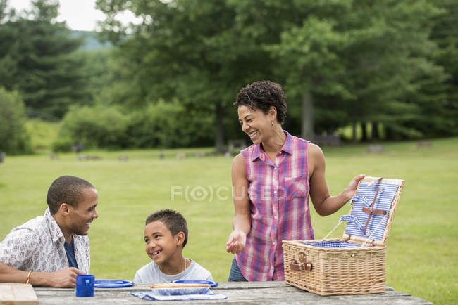 Familie sitzt mit Platten auf Picknick-Tisch im Wald. — Stockfoto